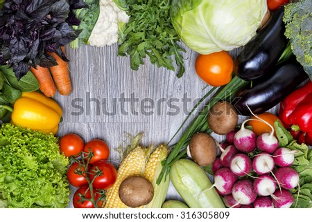 Fresh vegetables in the frame shape on wood background