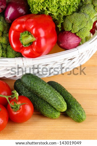 Fresh vegetables in white wicker basket on wooden background