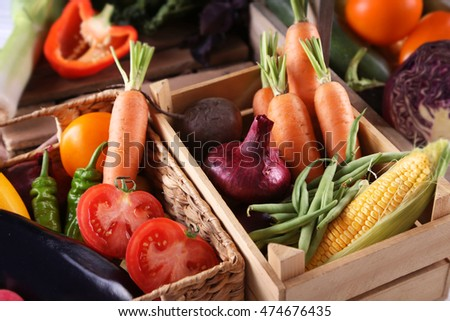 Fresh vegetables in wicker basket and wooden box