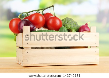 Fresh vegetables in wooden box on bright background
