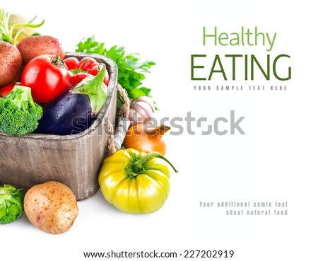 Fresh vegetables in wooden bucket with greens. Isolated on white background