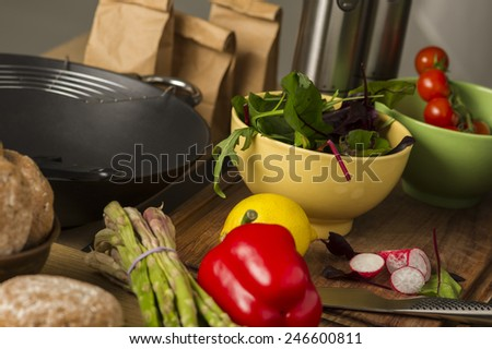 Fresh vegetables laid out on a kitchen counter ready to be used in preparing dinner with asparagus, red bell pepper, rocket and spinach na bowl, radish, lemon and cherry tomatoes
