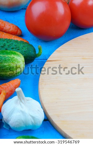 Fresh vegetables mix and cutting board on table