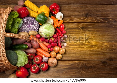 Fresh vegetables next to the overturned basket on the wooden surface. - stock photo