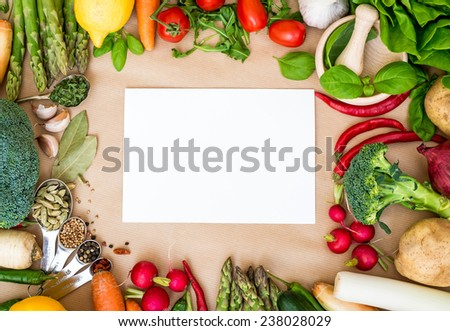 Fresh vegetables on a brown background with white paper, frame - stock photo
