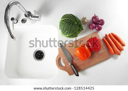 Fresh vegetables on a white kitchen table - stock photo
