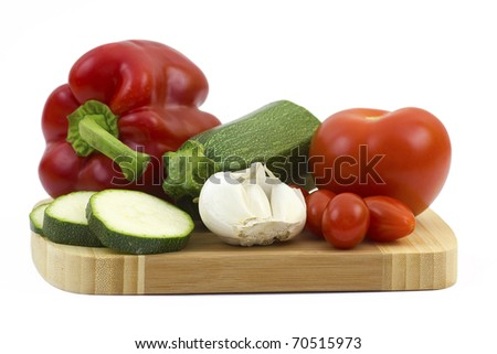 fresh vegetables on a wooden cutting board - stock photo