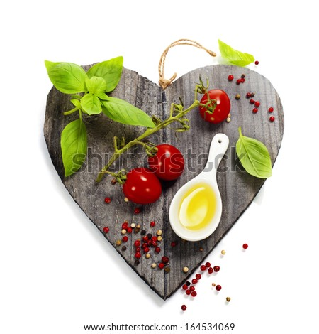 Fresh vegetables on heart shaped cutting board - stock photo