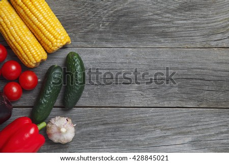 Fresh vegetables. Overhead view of a assortment of farm fresh vegetables, Red pepper, garlic, corn, tomatoes, cucumbers. - stock photo