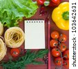 Fresh vegetables,pasta and a notebook on a wooden table - stock photo