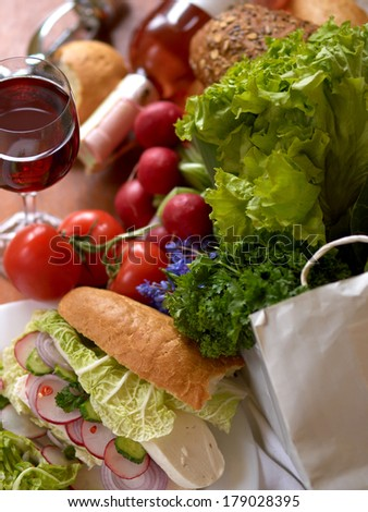 Fresh vegetables, sandwich with cheese,  glass of wine on wooden background with selective focus