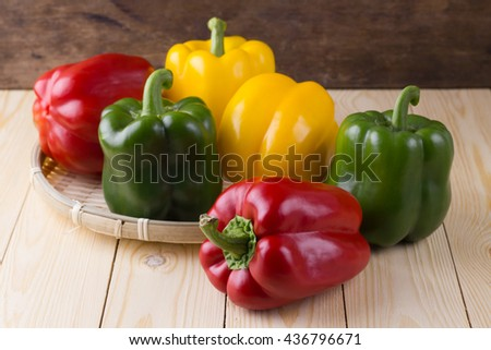 Fresh vegetables Three sweet Red, Yellow, Green Peppers in bamboo basket on wooden background - stock photo