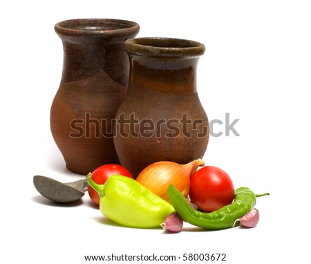 Fresh vegetables, two ceramic bowls and pewter spoon on a white background. - stock photo
