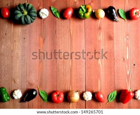 Fresh vegetables with basil leaves on brown wood background.