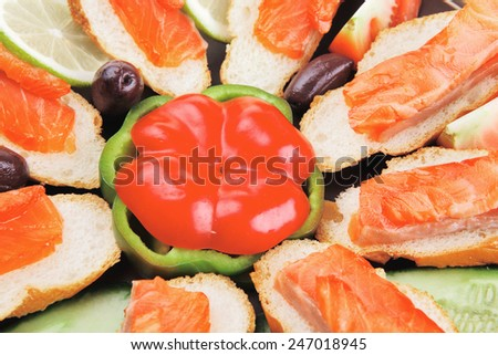 fresh vegetables with salmon on dark dish - stock photo