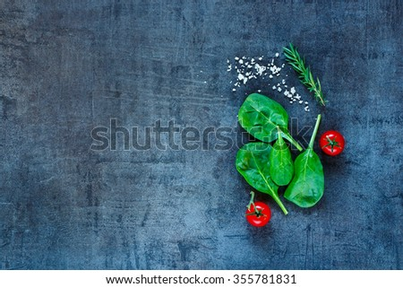Fresh vegetarian ingredients (spinach, tomatoes, grey salt and herbs) on dark vintage table, top view. Healthy food, vegan or diet nutrition concept. Background layout with free text space. - stock photo