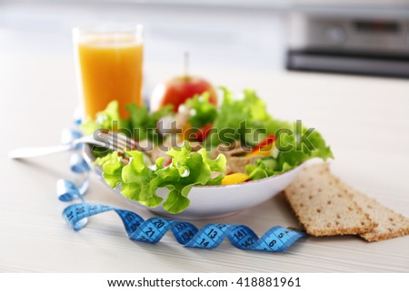 Fresh vegetarian salad and glass of juice on wooden table closeup - stock photo