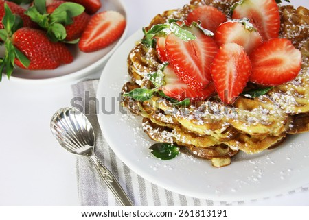 Fresh waffles with strawberries and icing sugar - stock photo