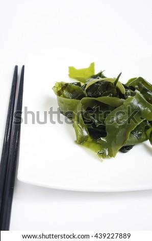 Fresh wakame seaweed salad and a pair of chopsticks - stock photo