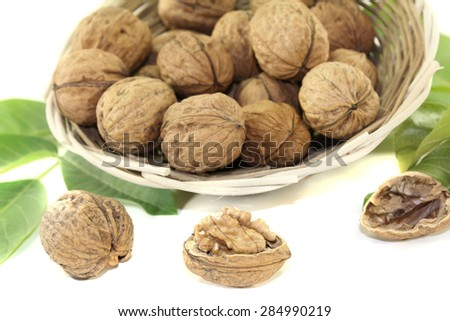 fresh walnuts with walnut leaves in a basket on bright background - stock photo