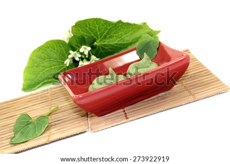 fresh Wasabi with leaf and flower in a red bowl