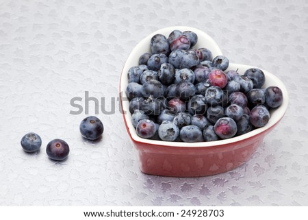 Fresh washed blueberries in a a red heart shaped bowl, on a silver leaf patterned surface