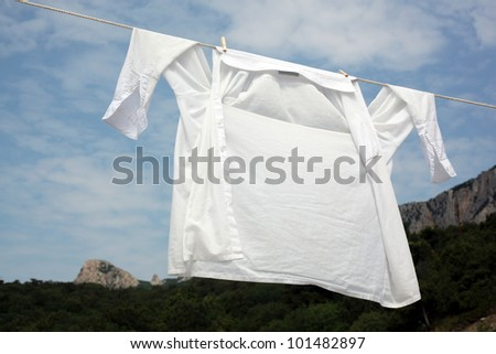 Fresh washed white shirt drying on a rope