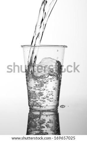 Fresh water filling transparent expendable cup made of plastic standing on white glass table with reflections, plenty bubbles of air in liquid. White background, vertical orientation, object in studio - stock photo