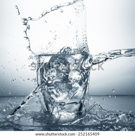 fresh water flowing in a glass with ice - stock photo