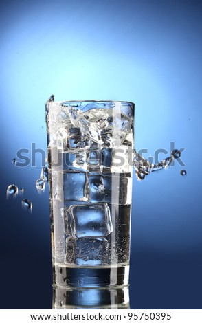 fresh water in glass with ice cubes on blue background - stock photo