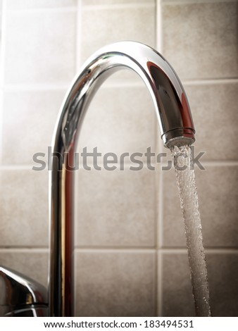 Fresh water is leaking from the tap. - stock photo