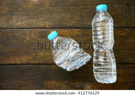 Fresh water on wooden background, plastic water bottle with blue cap on the wooden table, Recycle plastic of water bottle. - stock photo