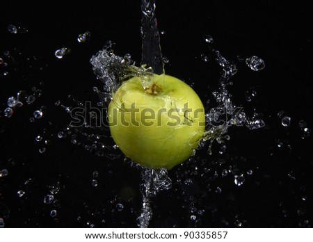 fresh water splash and green apple isolated on black