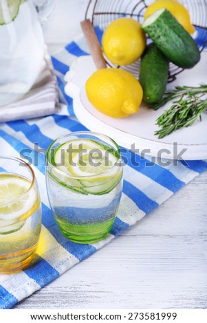 Fresh water with lemon and cucumber in glassware on wooden table, closeup - stock photo