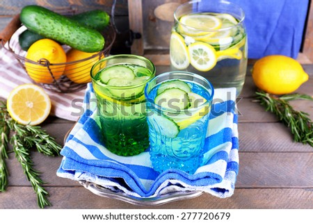Fresh water with lemon and cucumber in glassware with napkin on wooden background - stock photo