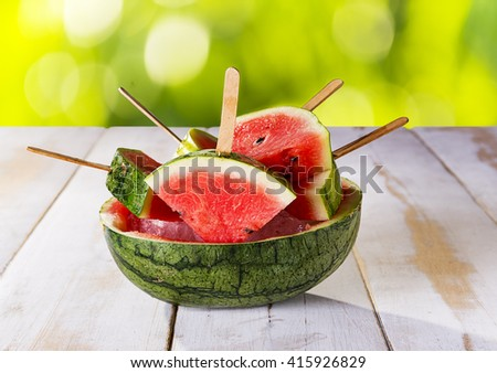 Fresh watermelon as popsicle on ice in a watermelon shell and white wood table. Light green background.