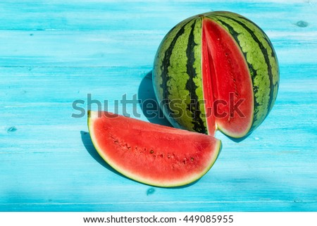 Fresh watermelon with one section sliced on blue wooden background - stock photo