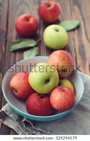 Fresh wet apples in a bowl on a wooden background - stock photo