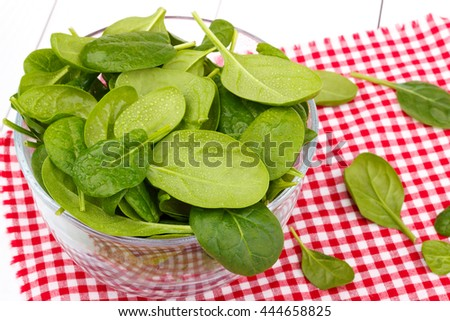 Fresh wet spinach in a bowl on red table cloth, close up, selective focus - stock photo