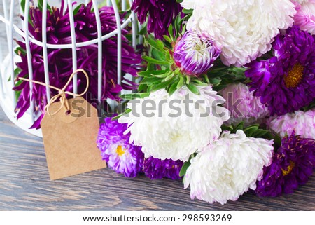 fresh white and violet aster flowers on table with empty paper tag - stock photo