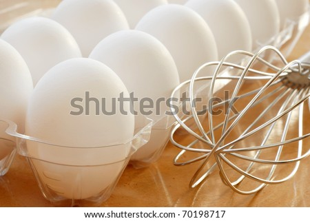 Fresh white eggs with stainless steel whisk.  Macro with shallow dof. - stock photo