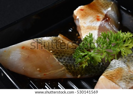 Fresh White fish on a black plate