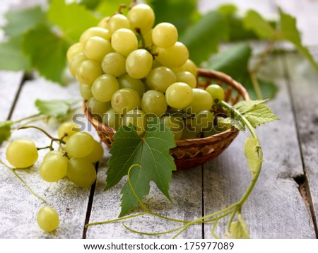 Fresh white grape in basket on wooden background with selective focus - stock photo