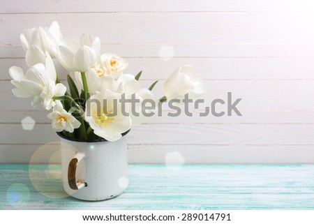 Fresh white tulips and daffodils in mug in ray of light  on turquoise painted planks against white wall. Selective focus. Place for text. - stock photo