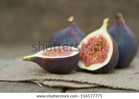 Fresh whole figs on wooden and hessian background