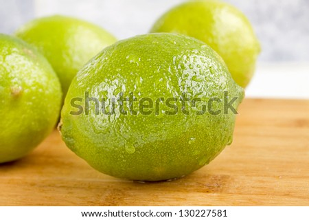 Fresh whole limes on a cutting board./Limes - stock photo