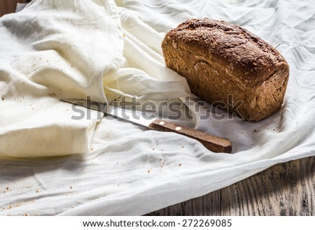 fresh whole rye bread on a white linen tablecloth, knife, rustic - stock photo