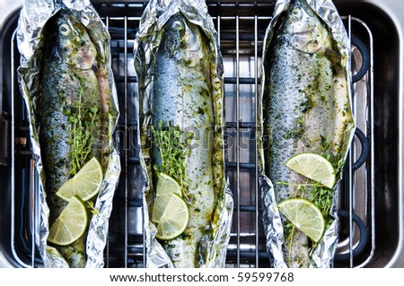 Fresh whole trout fishes richly decorated and marinated being grilled on an electric barbecue - stock photo