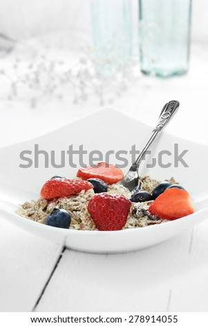 Fresh wholegrain and granola muesli with summer fruits against a bright background. The perfect image for your hotel breakfast menu cover design. Copy space. - stock photo