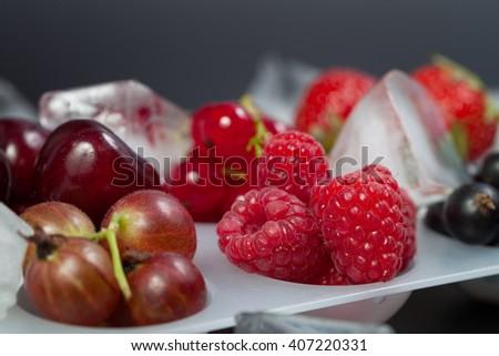 Fresh wild berries with ice cubes - stock photo